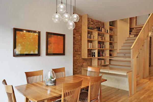 Sala de jantar com vários materiais: parede de tijolo, escadas de mármore e mesa e estante de madeira.