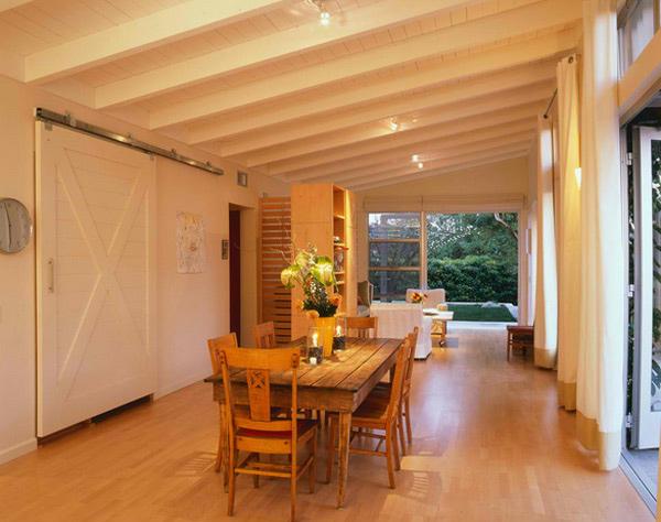Sala de jantar de madeira com chão de madeira e paredes e teto brancos.