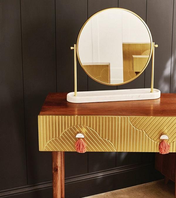 Penteadeira feita de madeira que tem um espelho como ponto focal.