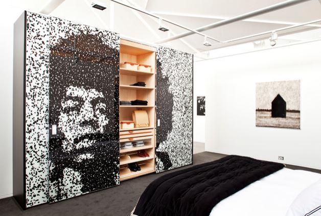 Guarda-roupa com porta de correr com retrato de Jimi Hendrix aberto, mostrando as prateleiras internas de madeira.