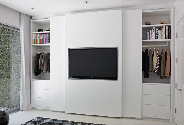 Guarda-roupa com porta deslizante com painel de TV no meio.