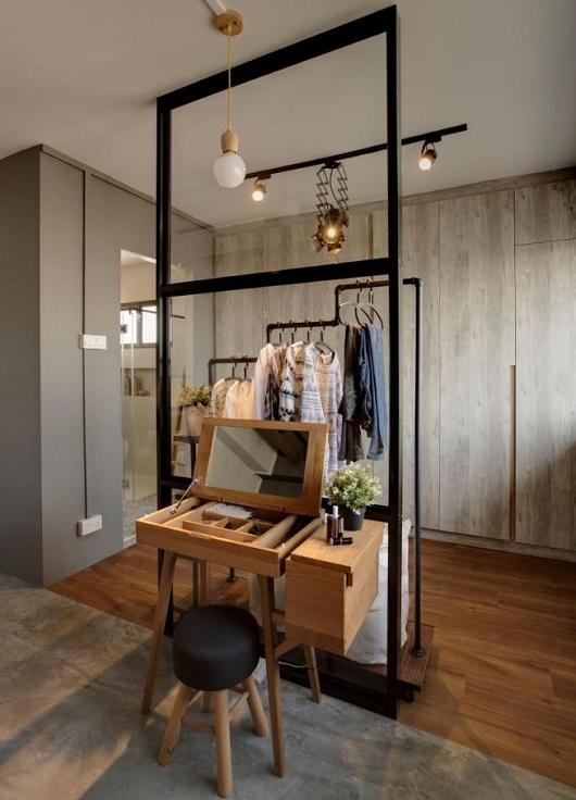Penteadeira feita de madeira como divisória entre o guarda-roupa e o quarto.