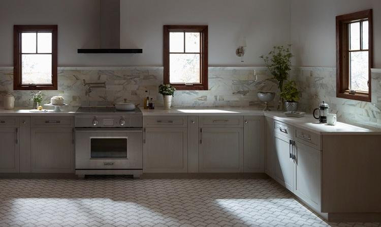 Cozinha com parede, bancada e chão claros e 3 janelas com molduras de madeira castanha.
