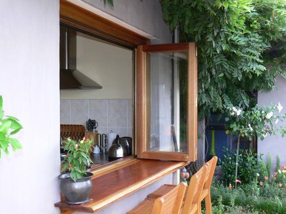 Janela de madeira para cozinha com balcão no jardim.