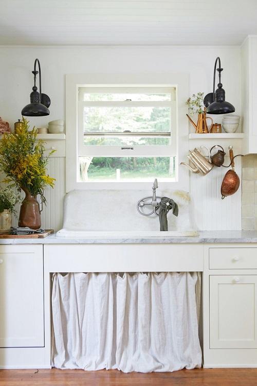 Cozinha pequena com janela de madeira branca em modelo guilhotina.