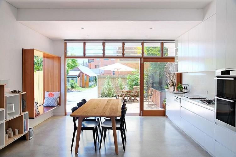 Janela grande madeira com banco em cozinha ampla.