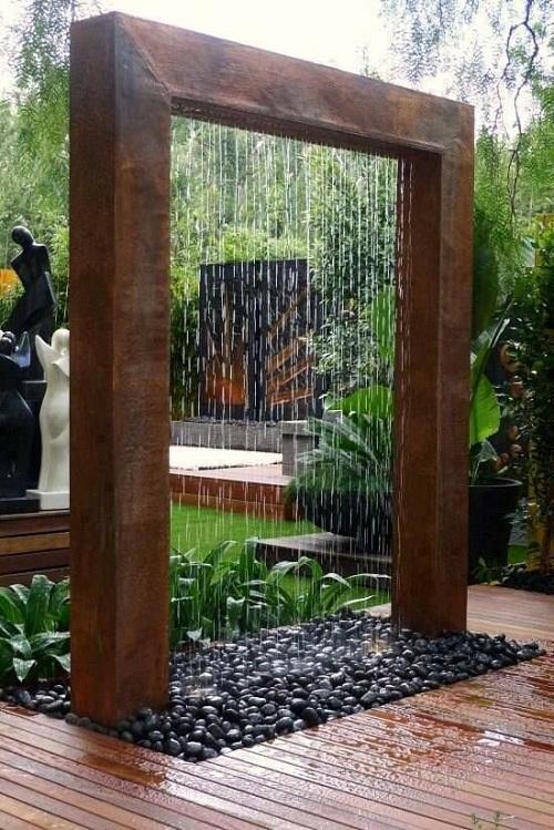 Parede de água com moldura de madeira em jardim.
