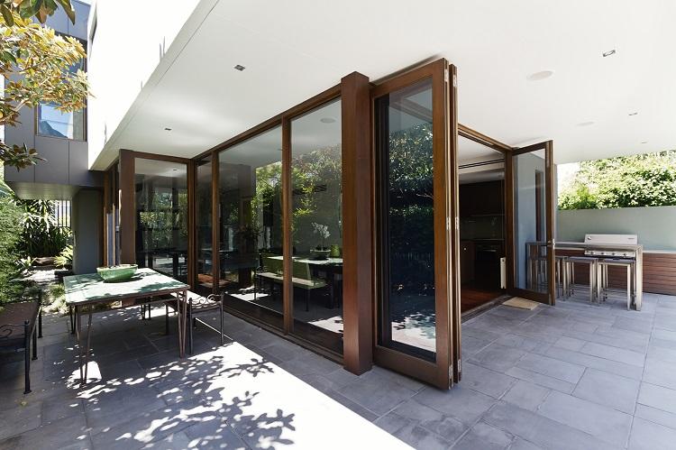 Porta articulada de madeira com vidro em frente do pátio externo.