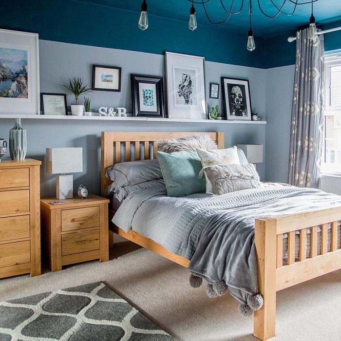 Quarto com móveis em madeira natural e teto azul.